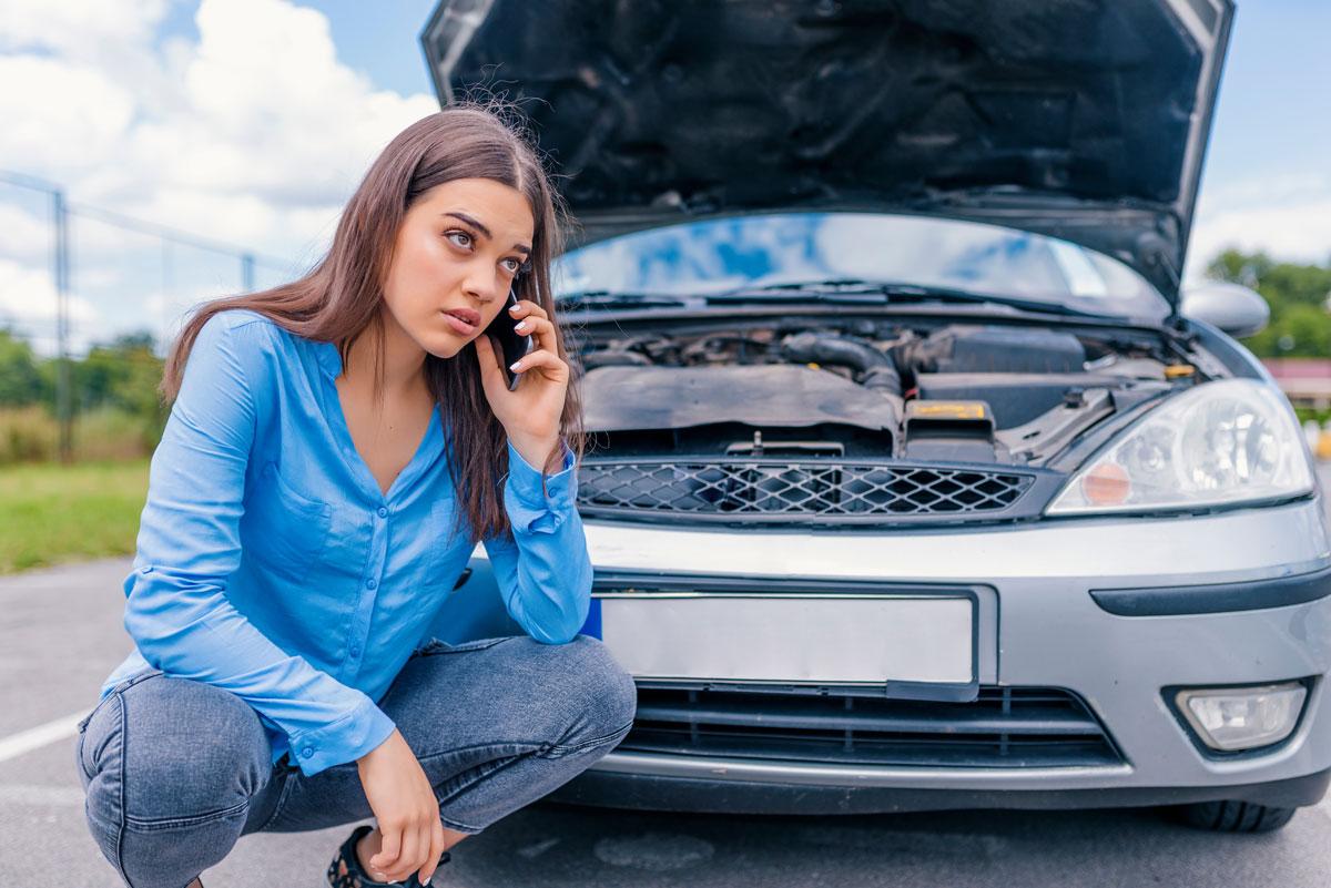 Frau telefoniert aufgrund von kaputtem Auto